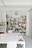 A large white table in an office with a bookshelf