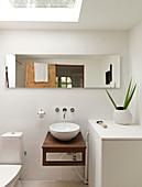 Horizontaler Spiegel und Dachfenster im kleinen Bad