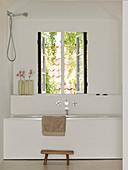 Hocker vor der Badewanne mit Sims unterm Fenster