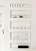 Regalkästen in weißer Wand mit Geschirr und Vorräten