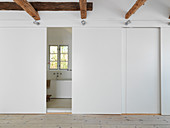 Hallway with wooden beams and sliding doors to the bathroom