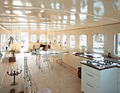Open kitchen with gas stove and dining table in a houseboat