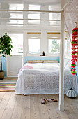 A flower necklace on the wall in a bedroom on a houseboat