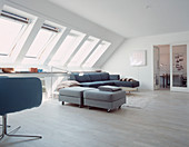 Upholstered stool on castors as a room divider in the living room with skylights