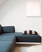 Black and white striped pillow on modern gray sofa