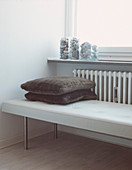 Industrial style upholstered bench in from of a radiator