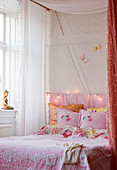 Romantic pink bed linen in the four-poster bed