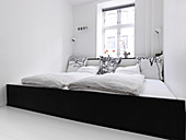 Breites Familienbett über die komplette Raumbreite im weißen Schlafzimmer