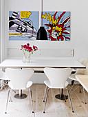 Weiße Designerstühle am Esstisch unter Comic-Bildern