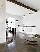 Rocking chair in an open living room with kitchenette and concrete floor