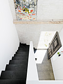 Bird's eye view of the black staircase and open front door