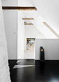 Black floor to the staircase with a sloping roof and wooden beams
