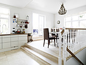 A view from an open-plan kitchen into a dining room two steps higher up