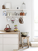 Storage containers on wall shelves in the white kitchen