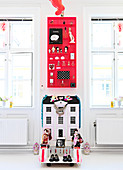 Red type case over dollhouse between two windows