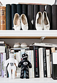 Ballet shoes and voodoo dolls on a bookshelf