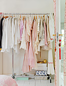 Romantic woman's dresses in pink and white on the coat rack