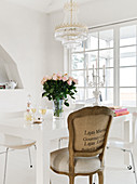 A baroque chair at a white table with a bouquet of roses under a chandelier