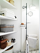 white shelf with towels and care products next to a towel rack