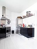 Schwarze Hochglanzküche mit Edelstahlarbeitsplatte in Altbauwohnung mit weißem Dielenboden