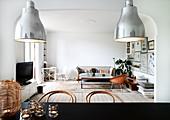 Blick über schwarzem Esstisch ins Wohnzimmer mit Schalenstuhl, Couchtisch und Couch