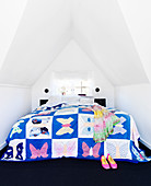 Patchwork quilt with butterflies on the bed under the eaves of the ceiling