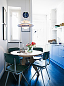 Retro chairs at the round table in a dine-in Kitchen with a dark wooden floor