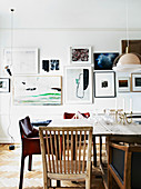 Different chairs at the dining table in front of the picture wall