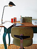 Old swivel chair in front of a wooden table used as a desk