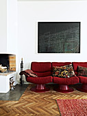 Red retro sofa under the black picture next to the fireplace
