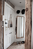 White entrance door with various locks and wall mirror in the entrance area with rustic wooden supports