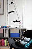 Schwarzer Stuhl mit Kissen vor Regal mit Büchern, darüber stilisierter Ast als Wanddekoration