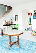 Achteckiger Holztisch auf blau-weißem Teppich im Vorraum mit weißem Holzboden