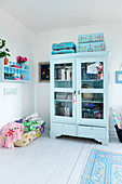 Light blue display cabinet with books, seat cushions, and suitcases