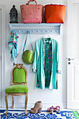 Colourful baskets, a lantern and clothing on a coat rack on the wall with a green chair below it