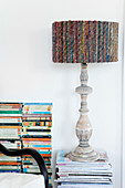 Table lamp with carved wooden base and colored lampshade on a pile of magazines