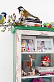 Alter Vitrinenschrank mit Familienfotos, Tierfiguren und Büchern