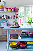 Light blue, open shelf with colorful dishes in an open plan kitchen-living room