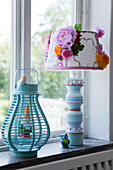 Turquoise lantern with garden gnome and table lamp with a decorated lampshade on a window sill