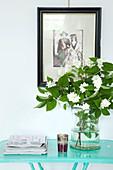 Zweig mit weißen Blüten in Glasvase auf türkisfarbenem Tisch, altes, gerahmtes Foto an der Wand