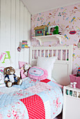 White wooden bed with patchwork blanket and plush stuffed animals in a girl's room