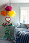 Colourful tulle flowers above bedside table next to bed in bedroom
