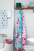 Colourful bathrobes in bathroom with white mosaic tiles