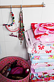 A stack of colourful towels, jewellery and a basket of cosmetic utensils