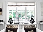 Zwei Sessel mit Kissen vor Fenster, Dekoration auf Fensterbank
