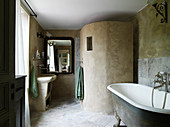 Vintage clawfoot bathtub, concrete shower screen, and vanity in the bathroom