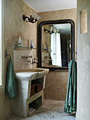Concrete vanity and wall mirror with antique frame in the bathroom