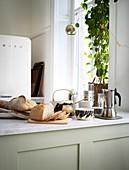 Aufgeschnittenes Brot, Kaffee und alles fürs Frühstück auf der Küchentheke