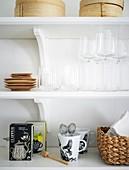 Ordnung im Regal mit Gläsern, Tee, Tassen und anderem Küchenzubehör
