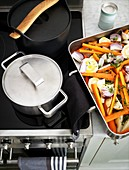casserole dish with vegetables next to the stove with two pots